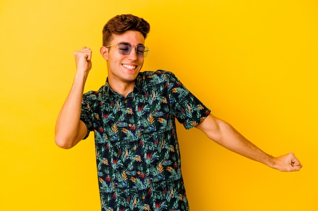 Junger kaukasischer mann, der ein hawaiihemd trägt, das auf gelbem hintergrund lokalisiert tanzt und spaß hat.