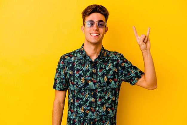 Junger kaukasischer mann, der ein hawaiihemd trägt, das auf gelbem hintergrund lokalisiert wird, der eine hörnergeste als ein revolutionskonzept zeigt.