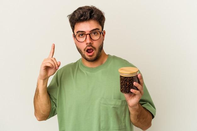 Junger kaukasischer mann, der ein kaffeeglas isoliert auf weißem hintergrund hält und eine großartige idee hat, konzept der kreativität.