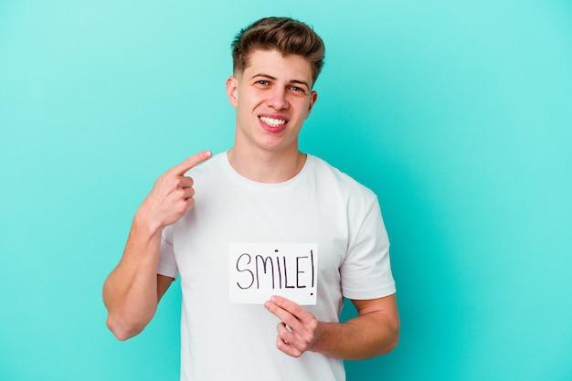 Junger kaukasischer mann, der ein lächelnplakat lokalisiert hält