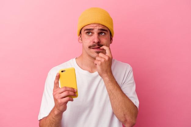 Junger kaukasischer mann, der ein mobiltelefon einzeln auf rosafarbenem hintergrund hält, entspannte sich beim nachdenken über etwas, das einen kopienraum betrachtet