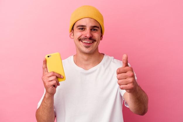 Junger kaukasischer mann, der ein mobiltelefon isoliert auf rosa hintergrund hält und lächelt und daumen hochhebt