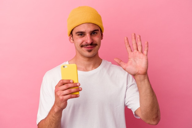 Junger kaukasischer mann, der ein mobiltelefon isoliert auf rosafarbenem hintergrund hält, lächelt fröhlich und zeigt nummer fünf mit den fingern.