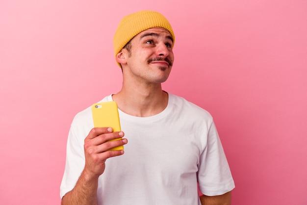 Junger kaukasischer mann, der ein mobiltelefon isoliert auf rosafarbenem hintergrund hält und davon träumt, ziele und zwecke zu erreichen