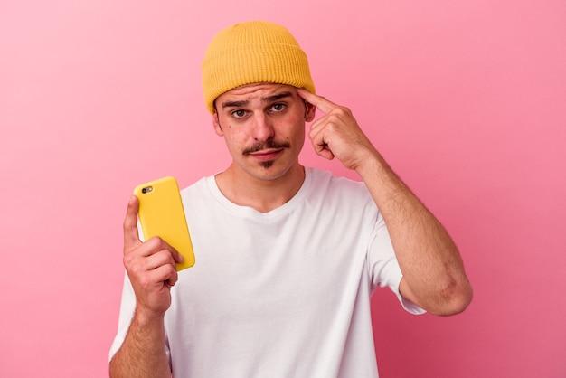 Junger kaukasischer mann, der ein mobiltelefon isoliert auf rosafarbenem hintergrund hält und mit dem finger auf den tempel zeigt, denkt, konzentriert sich auf eine aufgabe.