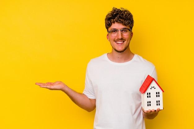 Junger kaukasischer mann, der ein modellhaus lokalisiert auf gelbem hintergrund hält, der einen kopienraum auf einer handfläche zeigt und eine andere hand auf taille hält.
