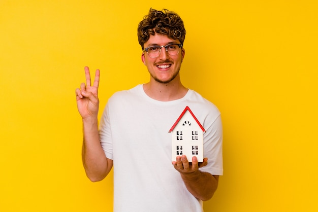 Junger kaukasischer mann, der ein modellhaus lokalisiert auf gelbem hintergrund hält, der nummer zwei mit den fingern zeigt.
