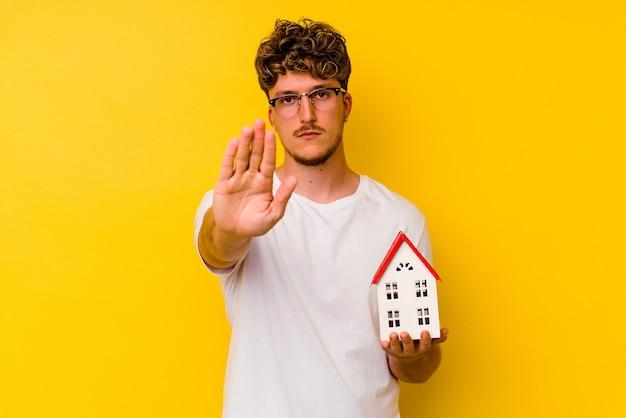Junger kaukasischer mann, der ein musterhaus isoliert auf gelbem hintergrund hält, das mit ausgestreckter hand steht und ein stoppschild zeigt und sie verhindert.
