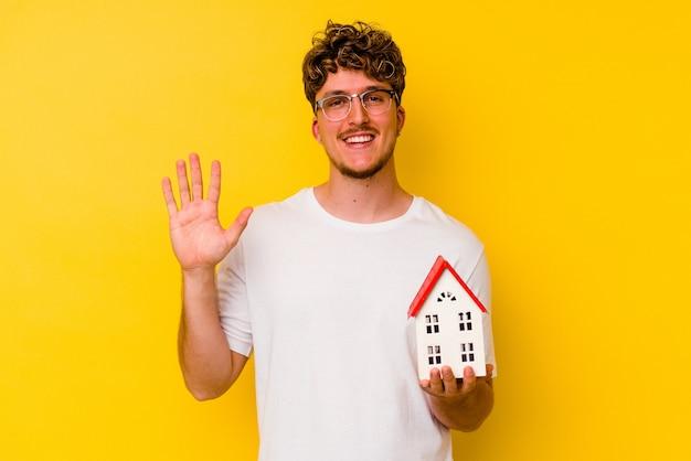 Junger kaukasischer mann, der ein musterhaus isoliert auf gelbem hintergrund hält, lächelt fröhlich und zeigt nummer fünf mit den fingern.