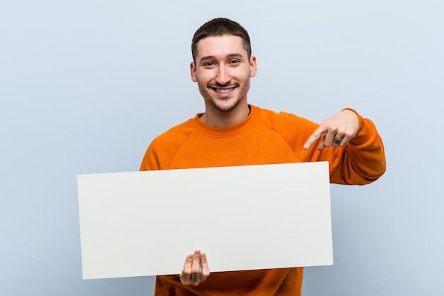 Junger kaukasischer mann, der ein plakat lächelt hält, freundlich zeigend mit dem zeigefinger weg.