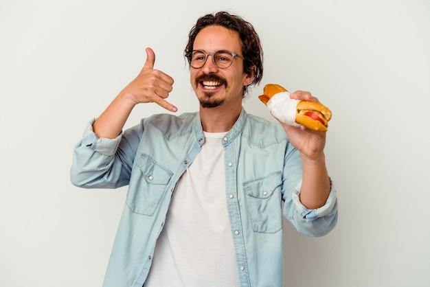 Junger kaukasischer mann, der ein sandwich hält, das eine handy-anrufgeste mit den fingern zeigt.