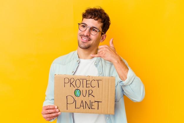 Junger kaukasischer mann, der ein schild zum schutz unseres planeten hält, das isoliert eine handy-anrufgeste mit den fingern zeigt.