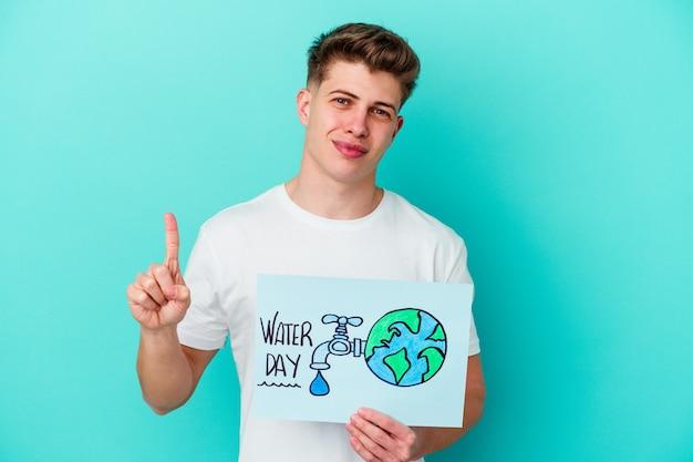Junger kaukasischer mann, der ein wassertagplakat lokalisiert auf blau hält