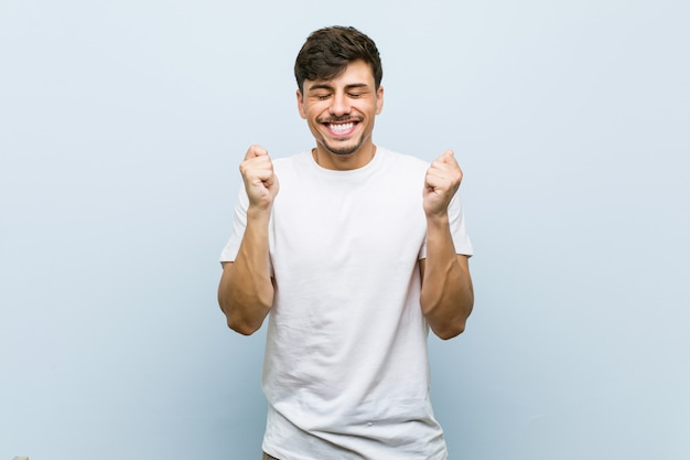 Junger kaukasischer mann, der ein weißes t-shirt anhebt die faust trägt, glücklich und erfolgreich sich fühlt. sieg.