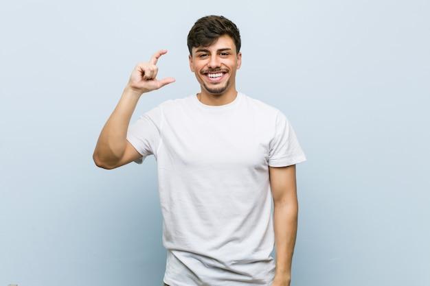 Junger kaukasischer mann, der ein weißes t-shirt hält etwas wenig mit den zeigefingern trägt, lächelt und überzeugt.