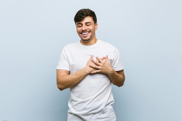 Junger kaukasischer mann, der ein weißes t-shirt lacht trägt, hände auf herzen, konzept des glückes halten.