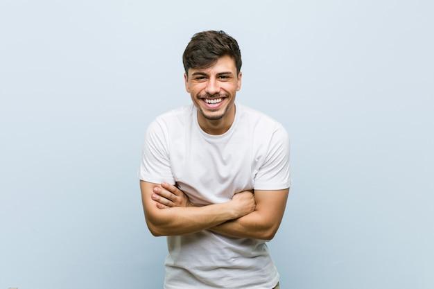Junger kaukasischer mann, der ein weißes t-shirt lacht und hat spaß trägt.