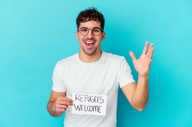 Junger kaukasischer mann, der ein willkommensplakat der flüchtlinge hält