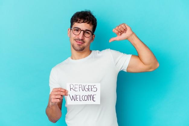 Junger kaukasischer mann, der ein willkommensplakat der flüchtlinge isoliert hält, fühlt sich stolz und selbstbewusst, beispiel zu folgen.