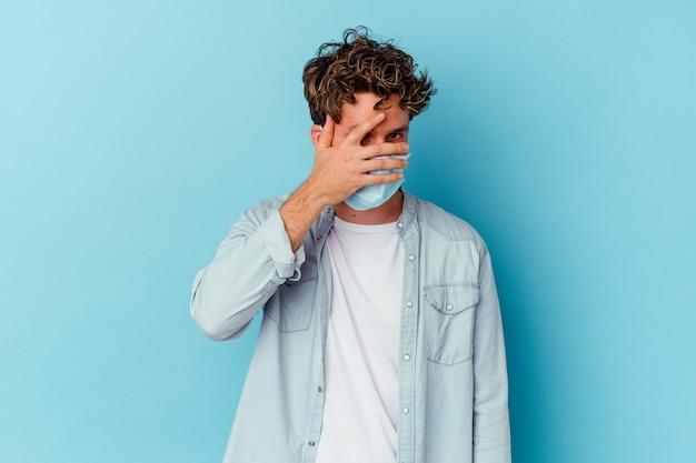 Junger kaukasischer mann, der eine antivirale maske trägt, die auf blauem blinzeln an der kamera durch finger lokalisiert wird, verlegenes bedeckendes gesicht.