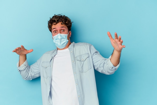 Junger kaukasischer mann, der eine antivirale maske trägt, die auf blauem hintergrund isoliert ist und aufgrund einer unmittelbar bevorstehenden gefahr schockiert ist Premium Fotos