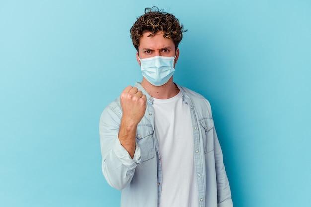 Junger kaukasischer mann, der eine antivirale maske trägt, die auf blauem hintergrund isoliert ist und die faust zur kamera zeigt, aggressiver gesichtsausdruck. Premium Fotos
