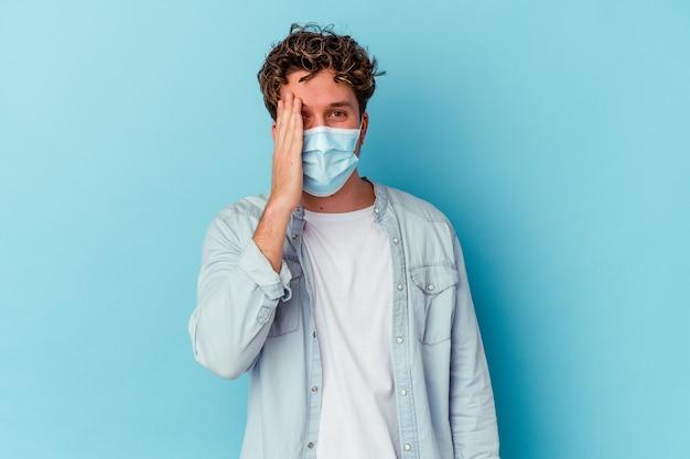 Junger kaukasischer mann, der eine antivirale maske trägt, die auf blauer wand lokalisiert wird, die spaß hat, die hälfte des gesichts mit handfläche bedeckt.