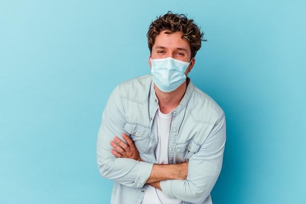 Junger kaukasischer mann, der eine antivirale maske trägt, die auf der blauen wand isoliert lacht und spaß hat.