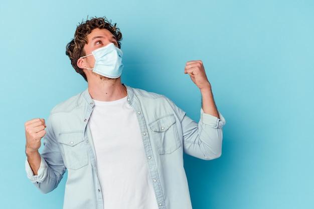 Junger kaukasischer mann, der eine antivirale maske trägt, die auf der blauen wand lokalisiert wird, die faust nach einem sieg, gewinnerkonzept erhebt.