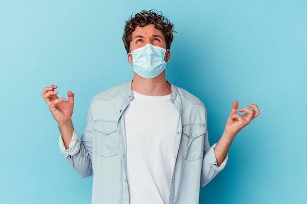 Junger kaukasischer mann, der eine antivirale maske trägt, die auf der blauen wand lokalisiert wird, die mit wut schreit.