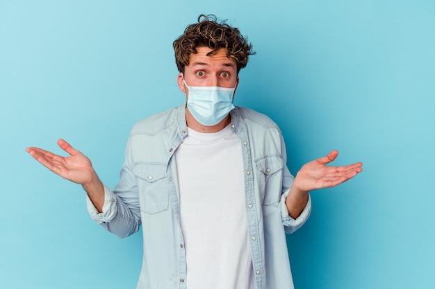 Junger kaukasischer mann, der eine antivirale maske trägt, die auf verwirrter und zweifelhafter achselzucken der blauen wand isoliert wird, um einen kopienraum zu halten.