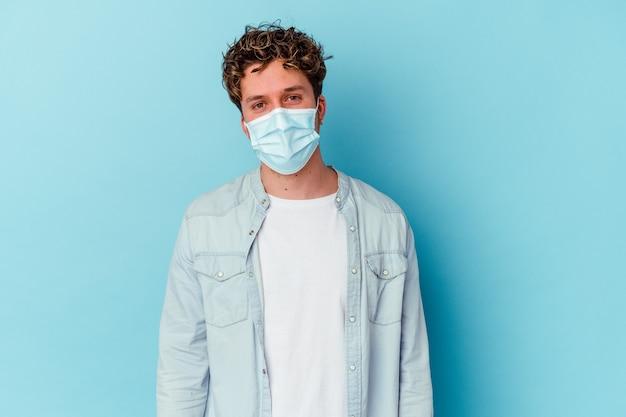 Junger kaukasischer mann, der eine antivirale maske trägt, lokalisiert auf blauer wand glücklich, lächelnd und fröhlich