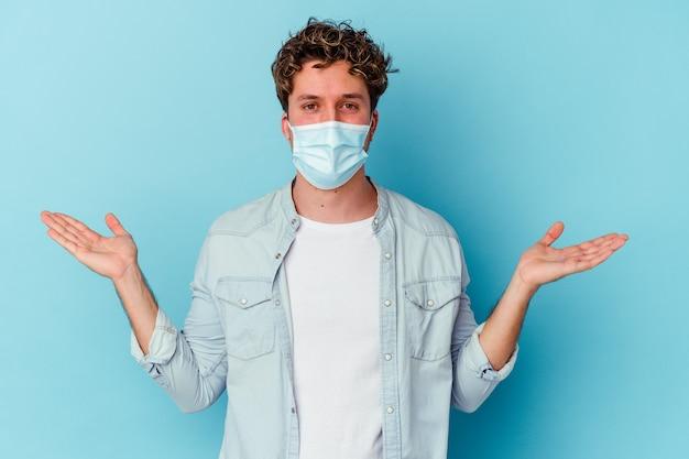 Junger kaukasischer mann, der eine auf blauem hintergrund isolierte antivirale maske trägt, macht mit armen skaliert, fühlt sich glücklich und selbstbewusst. Premium Fotos