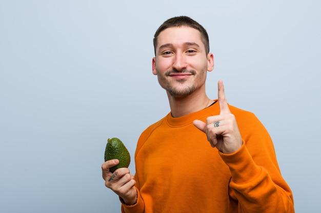 Junger kaukasischer mann, der eine avocado zeigt nummer eins mit dem finger hält.