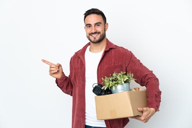 Junger kaukasischer mann, der eine bewegung macht, während er eine schachtel voll dinge aufnimmt, die auf weißem hintergrund lokalisiert sind, der finger zur seite zeigt