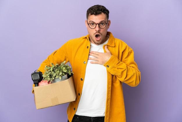 Junger kaukasischer mann, der eine bewegung macht, während er eine schachtel voller dinge aufhebt, die auf lila isoliert sind, überrascht und schockiert, während er richtig schaut
