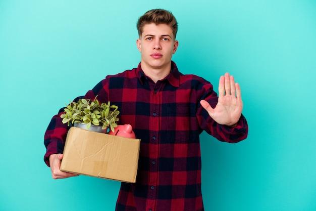 Junger kaukasischer mann, der eine box hält, die auf blauem hintergrund lokalisiert steht, der mit ausgestreckter hand steht, die stoppschild zeigt, das sie verhindert.