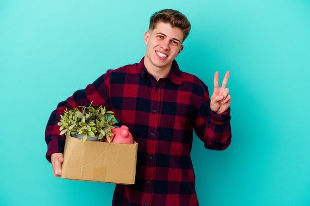 Junger kaukasischer mann, der eine box lokalisiert auf blauem hintergrund freudig und sorglos hält, ein friedenssymbol mit den fingern zeigend hält.