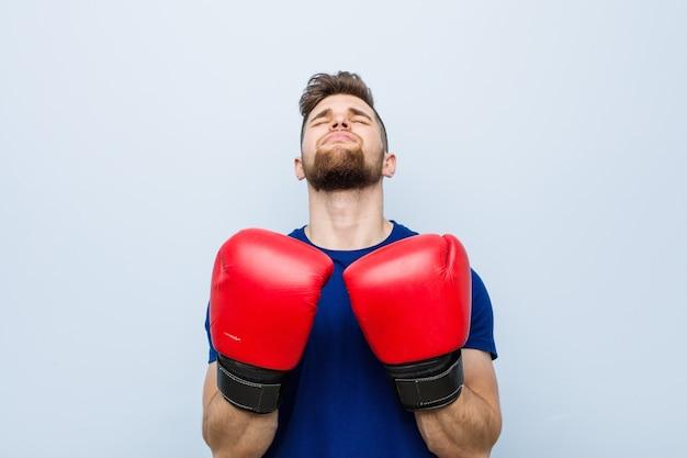Junger kaukasischer mann, der eine boxhandschuhe trägt