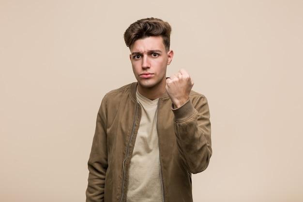 Junger kaukasischer mann, der eine braune jacke zeigt faust zur kamera, aggressiver gesichtsausdruck trägt.