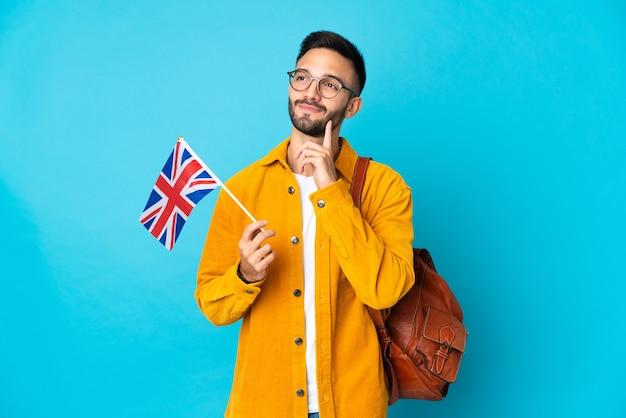 Junger kaukasischer mann, der eine britische flagge lokalisiert auf gelber wand hält, die eine idee beim nachschlagen denkt
