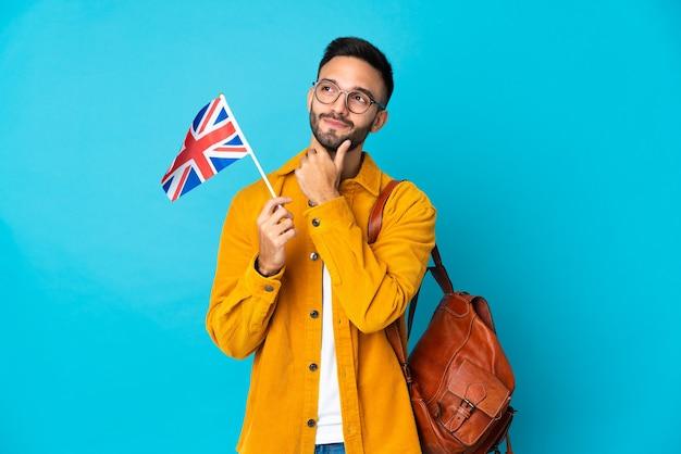 Junger kaukasischer mann, der eine britische flagge lokalisiert auf gelber wand hält und nach oben schaut
