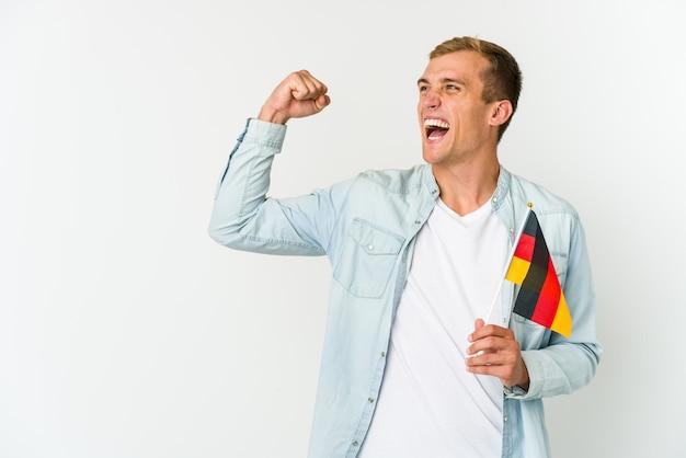 Junger kaukasischer mann, der eine deutsche flagge hält, die auf weißer erhabener faust nach einem sieg, gewinnerkonzept lokalisiert wird.