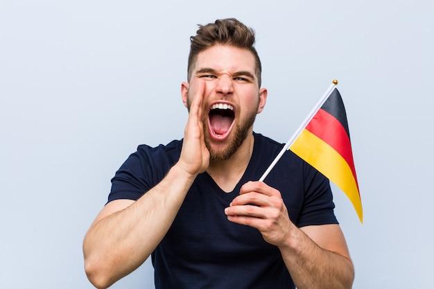 Junger kaukasischer mann, der eine deutschland-flagge schreit aufgeregte front hält.