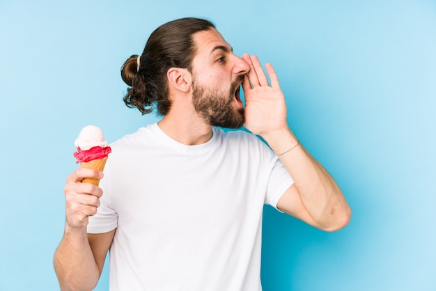 Junger kaukasischer mann, der eine eiscreme isst, die schreit und palme nahe geöffnetem mund hält.