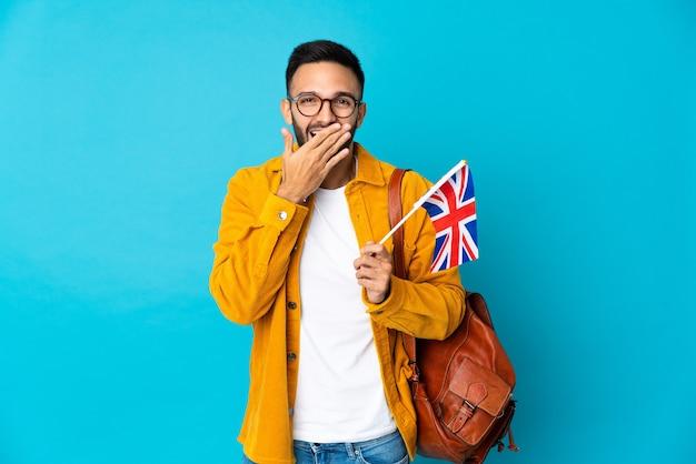 Junger kaukasischer mann, der eine flagge des vereinigten königreichs isoliert auf gelbem hintergrund hält, glücklich und lächelnd, die den mund mit der hand bedeckt