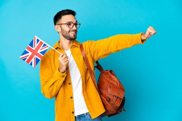 Junger kaukasischer mann, der eine flagge des vereinigten königreichs lokalisiert auf gelbem hintergrund hält, der eine daumen hoch geste gibt