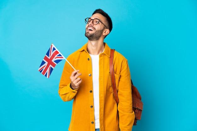 Junger kaukasischer mann, der eine flagge des vereinigten königreichs lokalisiert auf gelbem hintergrund hält, der eine idee beim nachschlagen denkt