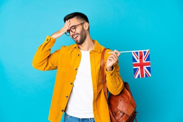 Junger kaukasischer mann, der eine flagge großbritanniens hält, die auf gelber wand isoliert wird, hat etwas erkannt und beabsichtigt die lösung