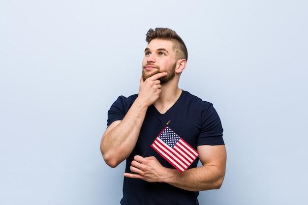 Junger kaukasischer mann, der eine flagge vereinigter staaten seitlich schaut mit zweifelhaftem und skeptischem ausdruck hält.